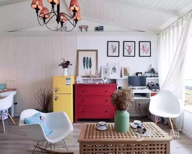 玄关处是白色的文化砖墙设计,白色的鞋柜与墙面视觉上融为一体,同时空出来的台面还能作为展示台使用。  客厅亮点多多,原本的平层空间被设计成了木质尖顶,好像冰雪中的独栋小屋,朴素清新。  亮黄色的迷你冰箱、经典红色斗柜点亮了整个空间,让白色的北欧风充满视觉的跳跃感,显得十分活泼。  一把伊姆斯摇椅,让疲惫的心在回家时能得到一份安宁的小憩。  桌上摆件。  为了进一步放大视觉空间,在厨房的设计上,设计师将其变为半开放式,在保留实用性的基础之上,给人更加通透的视觉体验。  米色的厨房台面搭配简约的白色橱柜,干