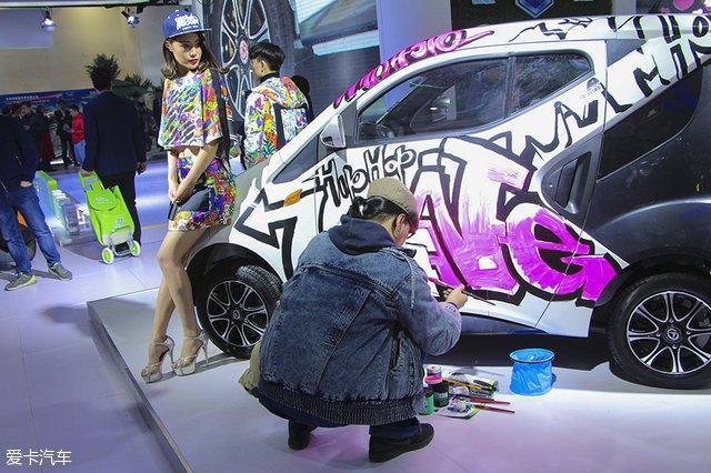 这位大哥手持丙烯颜料,在这辆造型别致的小车身上进行着自己的创作,身
