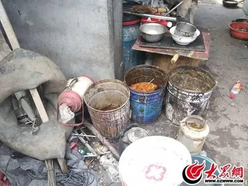院内装有剩菜剩饭的泔水桶散发着坏掉的酸味