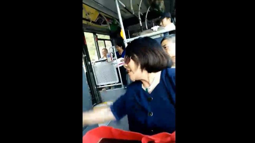 公交车一个妇女往地上吐痰扔纸,售票员让她捡起来不捡还骂人,引起了全车人的公愤