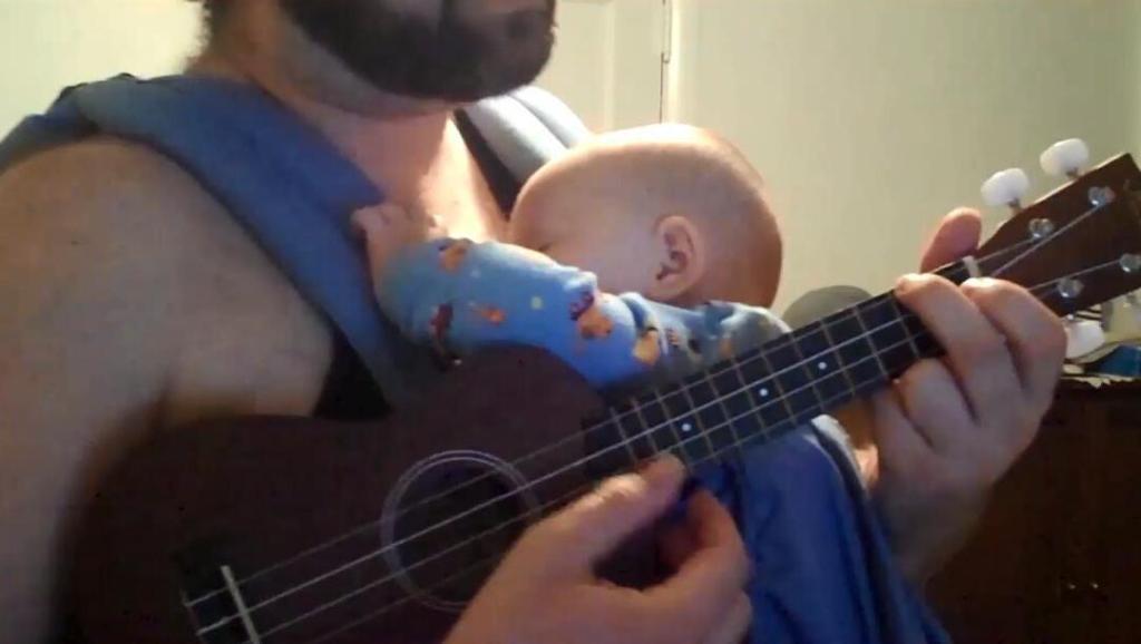 小宝宝困得哭闹,老爸不慌不忙弹唱尤克里里,没一会小娃就睡了