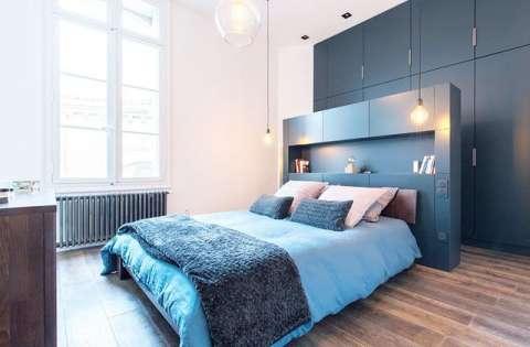卧室里背景墙,床铺以及柜子都是蓝色,为居住者提供了静谧的睡眠环境.