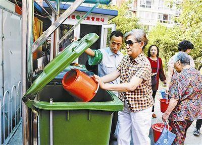 工作人员把厨余垃圾桶放在一个带有履带的装卸装置上
