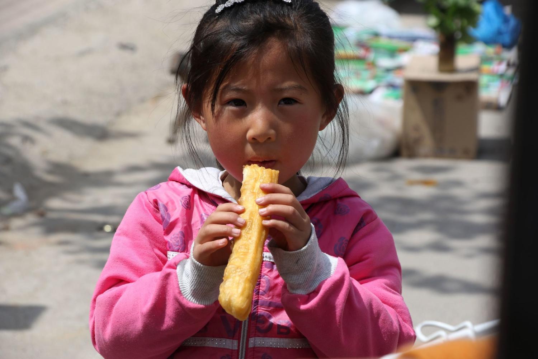 一名农村小女孩拿起妈妈刚买的油条就吃起来了,看她吃油条的样子就能