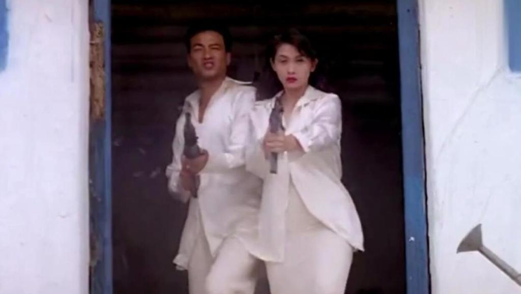 邱淑贞任达华两人身着一身白衣,手拿机关枪霸气登场,十分帅气