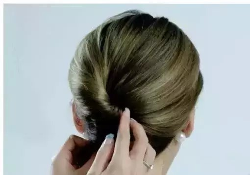 第一步 先用梳子将头发梳理通顺,将左侧的头发往侧边集中,并用黑色小
