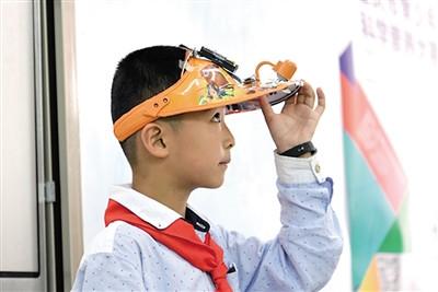 江北鲤鱼池小学的雷闵茜,展示了他设计的智能环保家居系统.图片