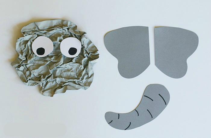 3,在褶皱的大象脸上,贴上两个眼睛,用卡纸剪出大象的大耳朵和长鼻子