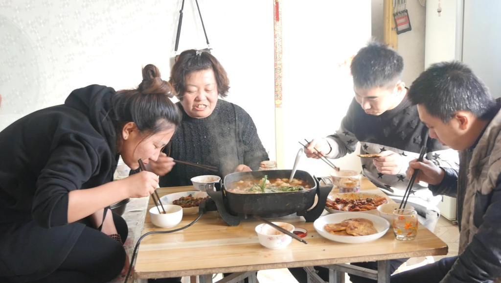 东北农村天冷下大雪,全家人围坐在炕上吃火锅,真是越吃越暖和!
