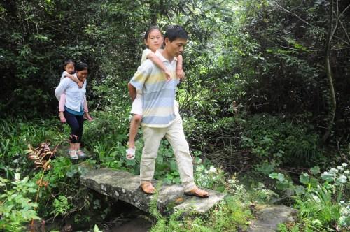 重庆石柱县桥头镇赵山村小学校谭艳红和陈益梅老师背学生过河.