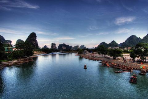 群山连绵,风景如画.乘坐竹筏,在山色秀美的遇龙河上欣赏山水田园风光.