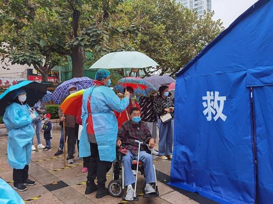 人民網直擊青島雨中核酸檢測現場 大傘之下有溫情-圖4