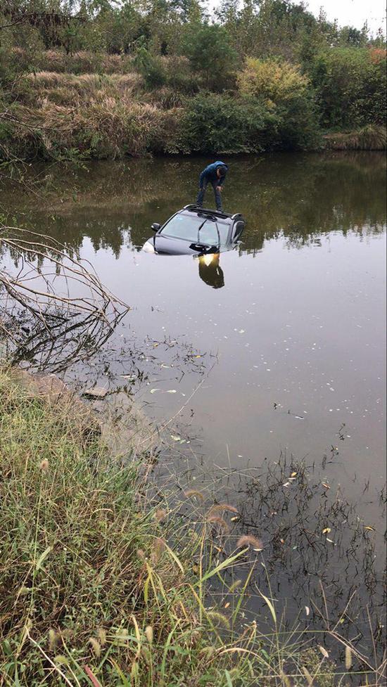 湖北一男子开车玩手机冲进水塘 民警及时将其救起