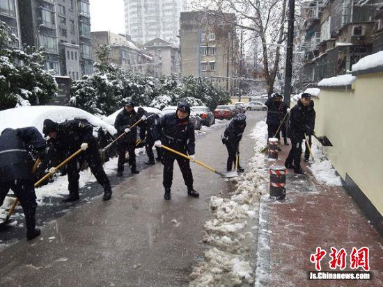 路上忙着撒盐、扫雪;还有人走街串巷,扫雪服务社区居民.-南京迎图片