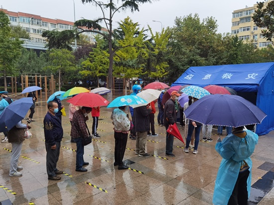 人民網直擊青島雨中核酸檢測現場 大傘之下有溫情-圖1