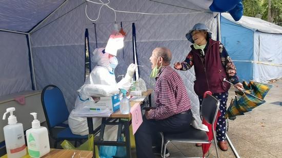 人民網直擊青島雨中核酸檢測現場 大傘之下有溫情-圖3