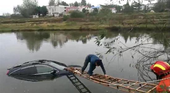 湖北一男子開車玩手機沖進水塘 民警及時將其救起